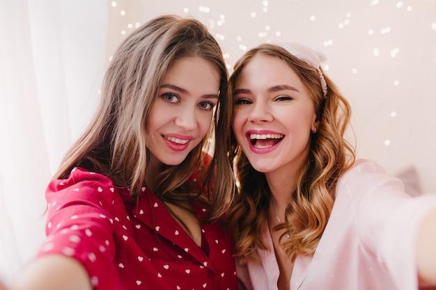 Bezauberndes braunhaariges mädchen im roten nachtanzug, das nahe schwester aufwirft. charmante kaukasische junge frau in der augenmaske, die selfie macht.