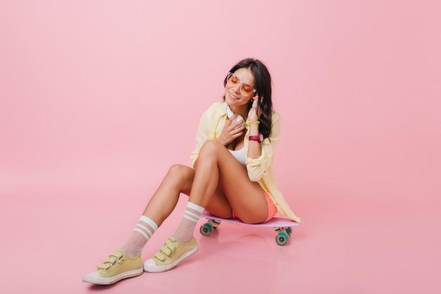 Bezauberndes dunkelhaariges weibliches model, das musik hört. charmantes brünettes lateinamerikanisches mädchen in der gelben jacke, die auf skateboard mit kopfhörern sitzt.