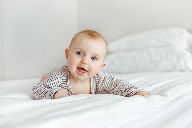 Bezauberndes glückliches baby auf weißem bett