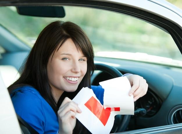Bezauberndes jugendlich mädchen des brunette, das in ihrem auto reißt ein l-zeichen sitzt