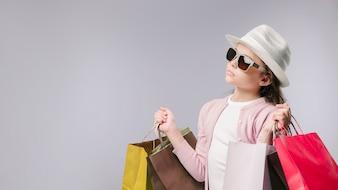Bezauberndes Mädchen mit Einkaufstaschen im Studio