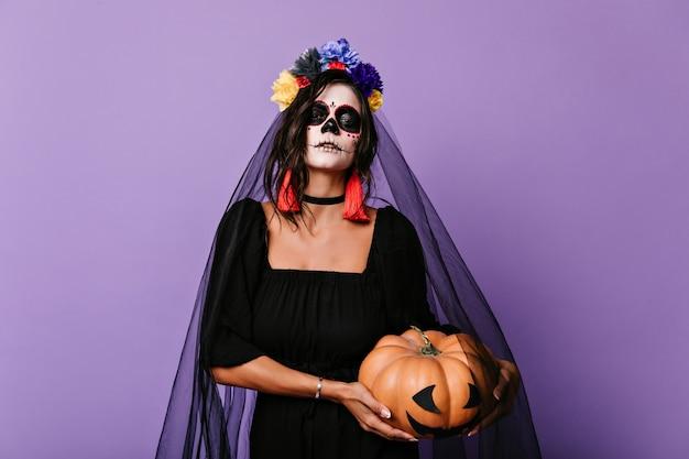 Bezauberndes mädchen mit gruseligem mexikanischem make-up, das sich auf halloween vorbereitet. innenaufnahme der romantischen toten braut im schwarzen schleier, der kürbis hält.