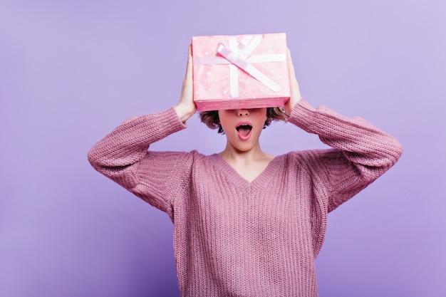 Bezauberndes mädchen trägt wollpullover isoliert auf lila wand mit rosa geschenkbox. innenfoto der glücklichen kurzhaarigen frau, die spaß mit neujahrsgeschenk hat.