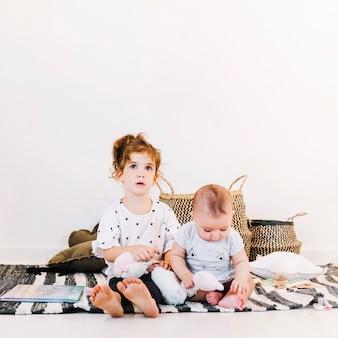 Bezauberndes mädchen und nettes baby in der kindertagesstätte