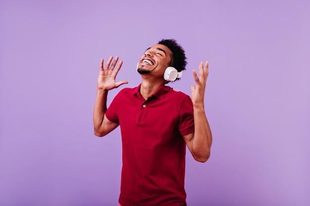 Bezauberndes männliches model mit musik, die braune haut hört. abschreckender afrikanischer typ.