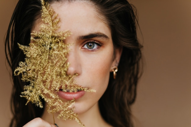 Bezauberndes weißes mädchen mit trendigem schmuck, der mit pflanze aufwirft. nahaufnahme des verblüfften weiblichen modells mit goldenem zubehör und grünem blatt.