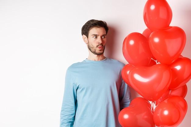 Beziehung. junger mann, der verwirrt auf herzballon schaut, verwirrt am valentinstag, stehend auf weißem hintergrund