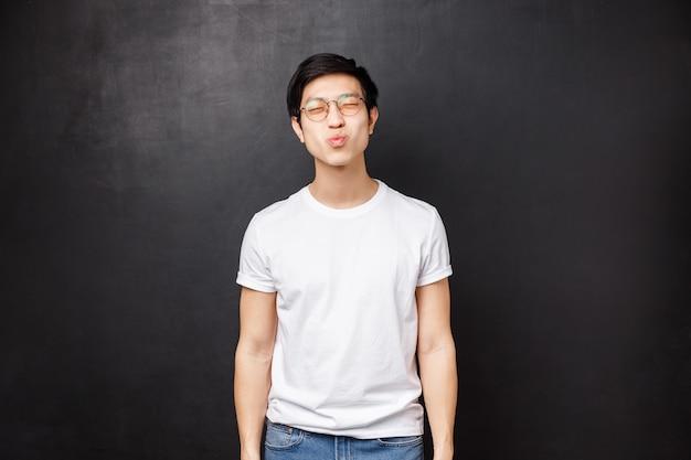 Beziehungs-, romantik- und paarkonzept. netter dummer asiatischer freund schließen augen und schmollende lippen, die für den ersten kuss vorbereitet werden, wollen kichern und lächeln, sein erstes date mit mädchen haben, das er liebt
