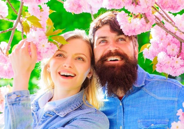 Beziehungskonzept. glückliches paar in der nähe von blühenden sakura. lächelnde familie verbringt zeit im frühlingsgarten.
