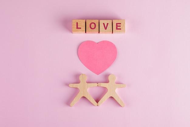 Beziehungskonzept mit papierschnittherz, holzwürfeln, menschlichen modellen auf rosa tisch flach liegen.