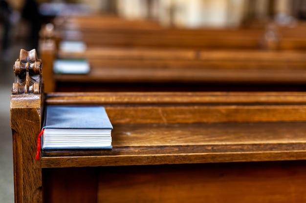 Bibel auf einer leeren bank in einer kirche vor einem gottesdienst.