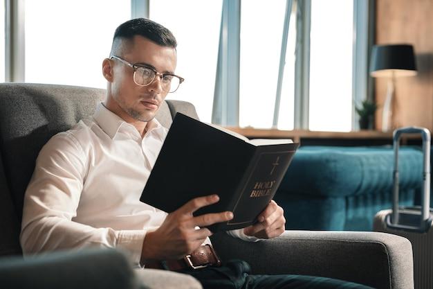 Bibel halten. dunkelhaariger mann, der eine brille trägt, die die heilige bibel hält, die lesezeit genießt