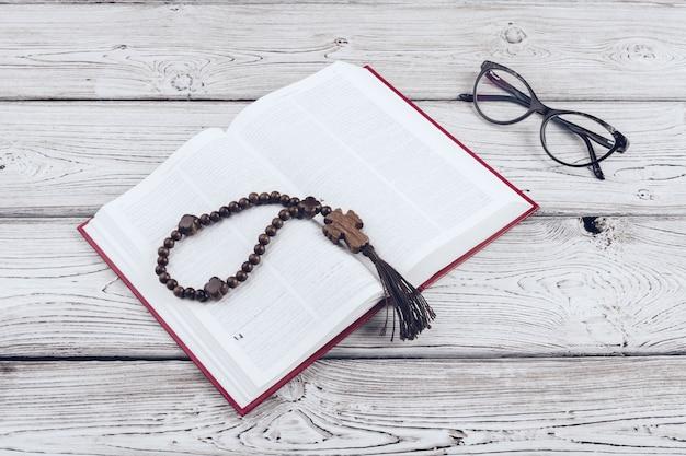 Bibel und das kruzifix auf einem weißen holztisch