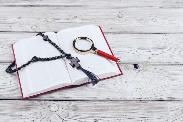 Bibel und das kruzifix auf weißem holztisch.