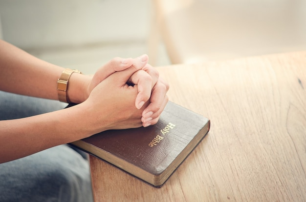 Bibelgebet falten sie ihre hände in der bibel beten geistlich und religiös kommunizieren sie mit gott, liebe und vergebung.