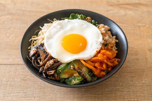 Bibimbap, koreanischer würziger salat mit reis und spiegelei - traditionell koreanische küche