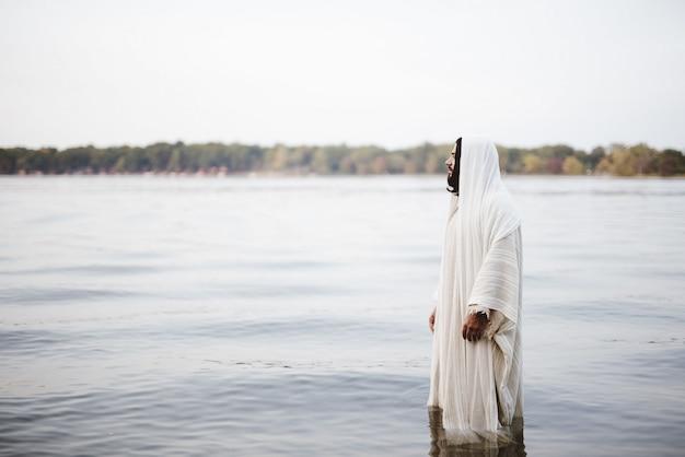 Biblische szene - von jesus christus, der im wasser mit einem unscharfen hintergrund steht