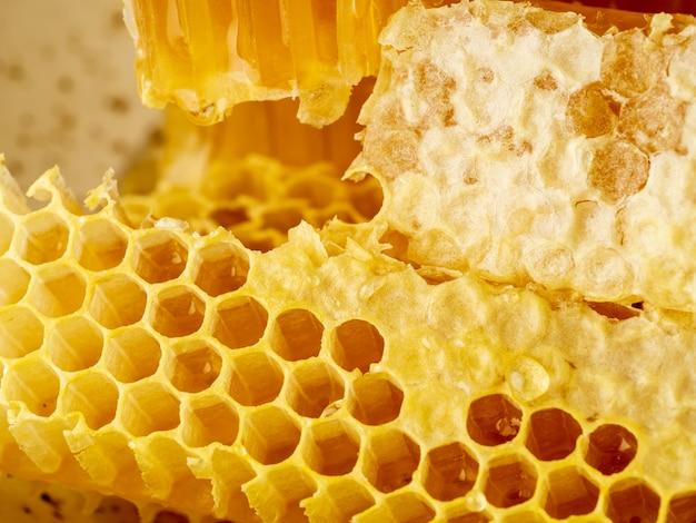 Bienenbienenwabennahaufnahme, frischer fadenziehender süßer honig, makro