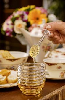 Bienenhonig in glasbehälter und hände, die honigtau auf einem tisch im vintage-stil halten