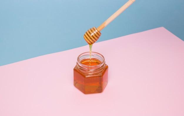 Bienenhonig tropft von einem holzspatel in ein glas
