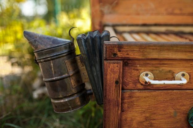 Bienenraucher installiert auf hölzernem behive. technologie der begasung von bienen. berauschender rauch für eine sichere honigproduktion.