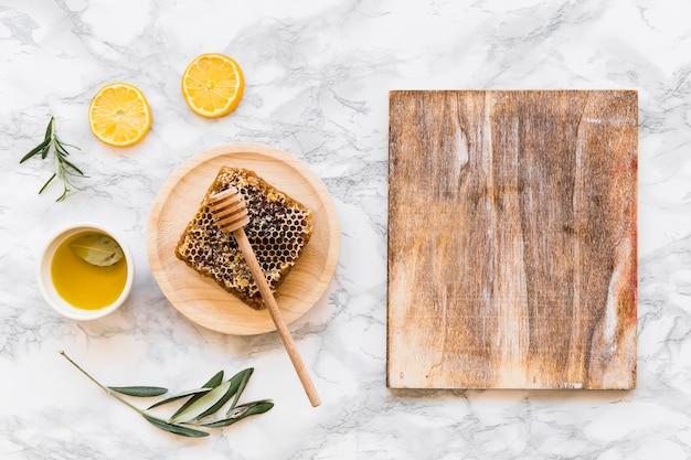 Bienenwabe mit olivenöl mit hölzernem hackendem brett