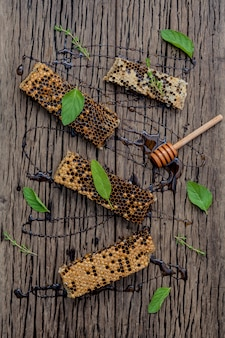 Bienenwabe und honig mit kräutern auf dunklem hölzernem hintergrund.