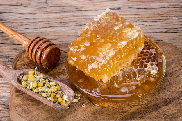 Bienenwaben und honiglöffel auf einem hölzernen brett und einer tabelle