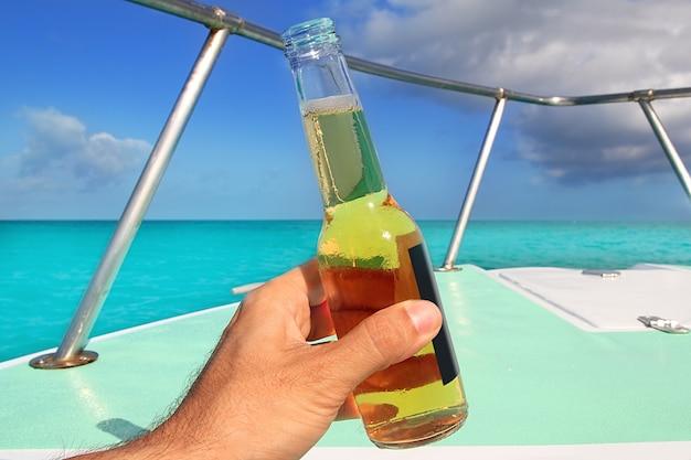 Bier an hand karibisch im bootsbogentürkismeer