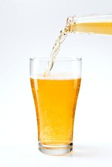Bier, das aus einer bierflasche in ein glas gießt