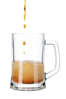 Bier, das aus flasche in das glas getrennt auf weiß gießt
