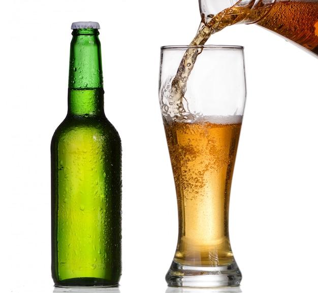 Bier, das in ein glas von einer grünen flasche gießt