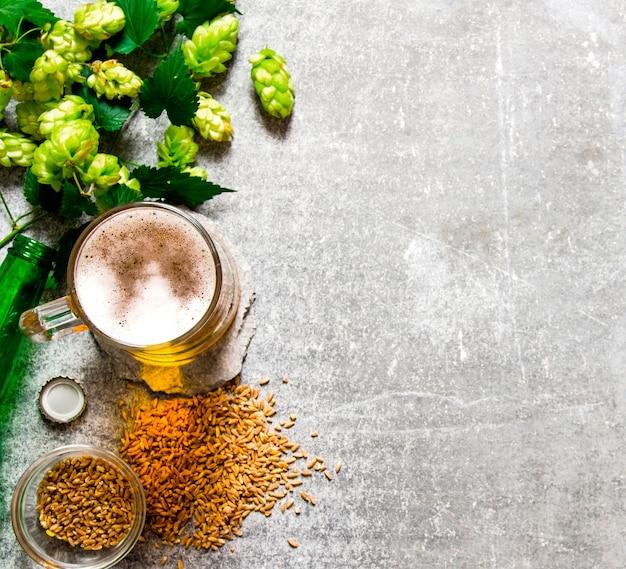 Bier, grüner hopfen und malz auf einer steinoberfläche. draufsicht