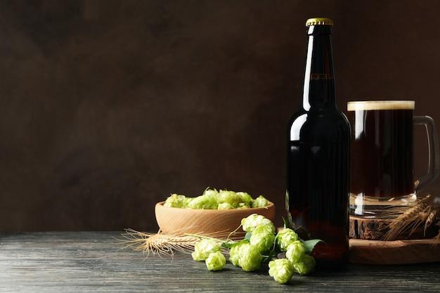 Bier, hopfen und weizen auf holztisch vor braunem hintergrund