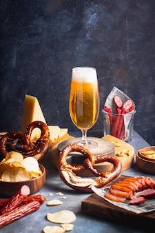 Bier im glas mit auswahl an biersnack brezelkäse kartoffelchips würstchen