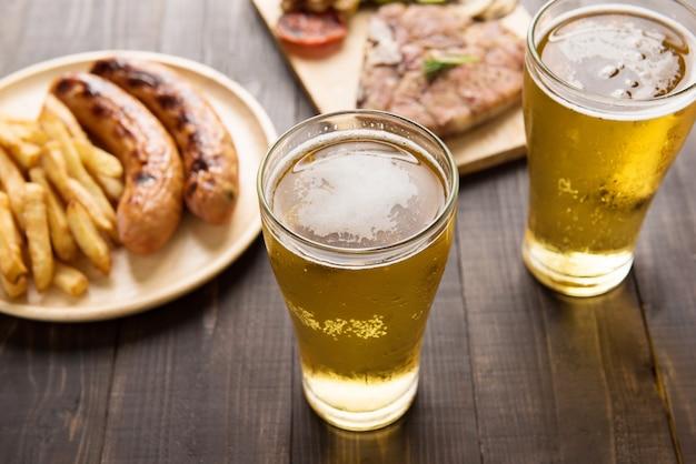 Bier im glas mit gourmetsteak und pommes frites auf hölzernem hintergrund
