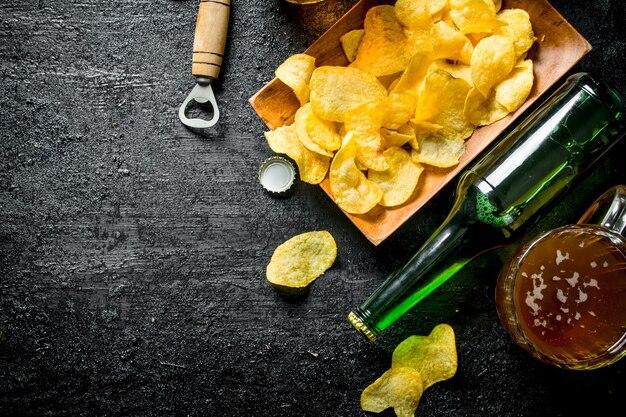 Bier in bechern und eine flasche pommes auf einem teller. auf schwarzem rustikalem hintergrund