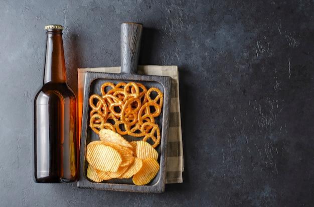 Bier in dunklen glasflaschen und salzigen snacks. dunkler konkreter hintergrund. draufsicht. freier platz für text.