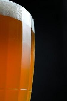Bier in einem glas auf schwarzem hintergrund.