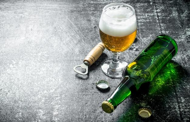 Bier in einem glas mit öffner. auf schwarzem rustikalem tisch