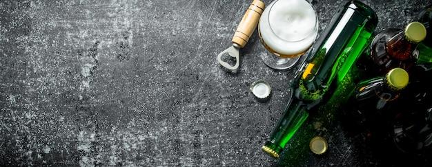 Bier in einem glas und einer glasflasche mit öffner auf rustikalem tisch