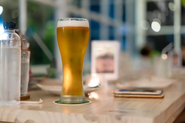 Bier in einem hohen glas, das auf den tisch gelegt wird.