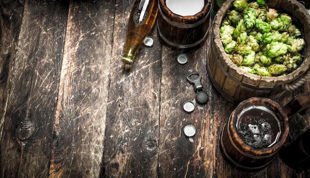 Bier in einem holzbecher mit grünem hopfen. auf einem hölzernen hintergrund.