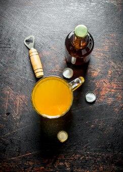 Bier in einer glasschale und einer flasche. auf dunklem rustikalem tisch
