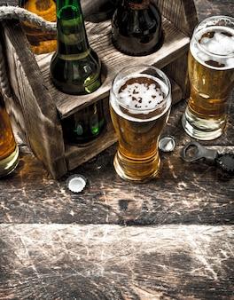 Bier in einer schachtel mit gläsern. auf einem holztisch.