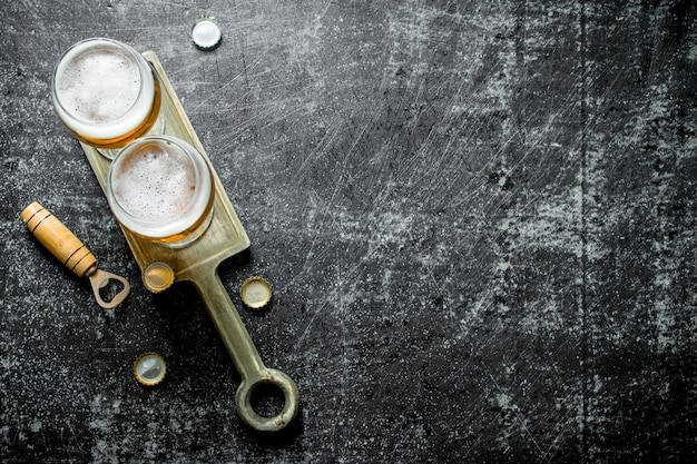 Bier in gläsern auf dem stand. auf rustikalem hintergrund