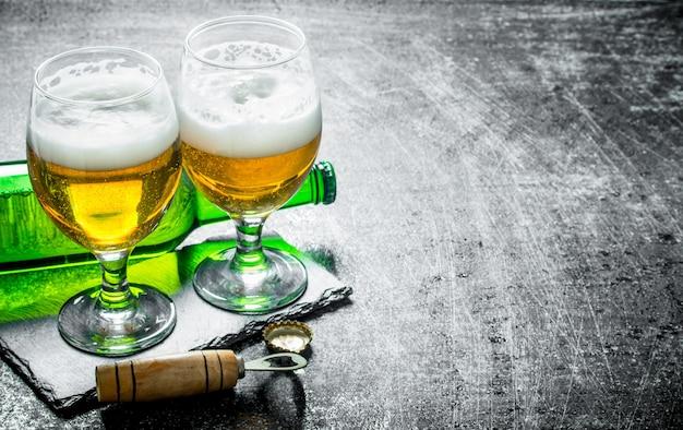 Bier in gläsern auf einem ständer mit öffner. auf schwarzem rustikalem tisch