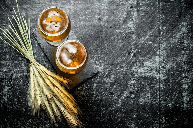 Bier in gläsern auf einem ständer und ein paar ährchen. auf schwarzer rustikaler oberfläche