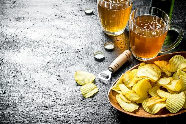 Bier in glasbechern mit pommes auf einem teller. auf schwarzem rustikalem tisch
