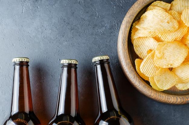 Bier in glasflaschen und gesalzene kartoffelchips. dunkler konkreter hintergrund. speicherplatz kopieren.